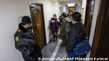 An Azerbaijani policeman, left, guards as journalists gather at the Radio Free Europe headquarters in Baku, Azerbaijan on Friday, Dec. 26, 2014. The radio station funded by the U.S. government says its office in Azerbaijan's capital of Baku has been raided by prosecutors who claim to have a court decision to shut it down. Radio Free Europe/Radio Liberty on Friday quoted the director of its Azerbaijani service saying that the office has been locked down since early morning by prosecutors and armed police. (AP Photo/Aziz Karimov)