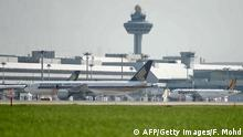 This photograph taken on July 29, 2014 shows a Singapore Airlines passenger plane (L) parked at a terminal next to a Tiger Air plane (R) at Changi International Airport in Singapore. Singapore Airlines is expected on July 30 to release earnings report for the 2014 financial first quarter. AFP PHOTO / Fyrol Mohd (Photo credit should read FYROL MOHD/AFP/Getty Images)