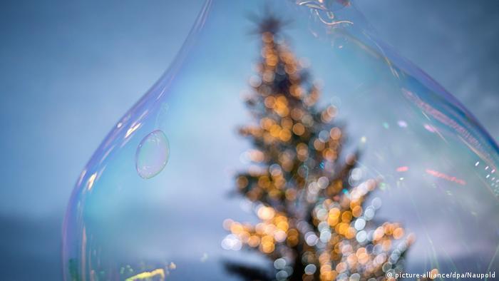 Durch eine Seifenblase ist verschwommen ein Weihnachtsbaum zu erkennen