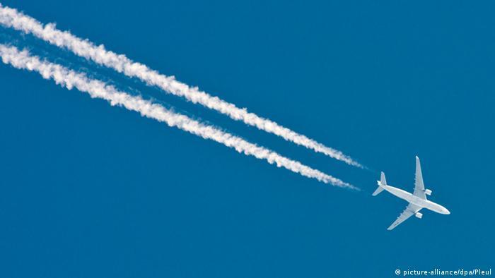 A plane streaks across a deep blue sky, leaving white lines in its wake
