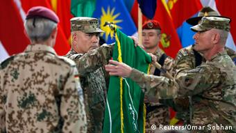 US General John Campbell (C), commander of NATO-led International Security Assistance Force (ISAF), folds the flag of the ISAF during the change of mission ceremony in Kabul, December 28, 2014 (Photo: REUTERS/Omar Sobhani)
