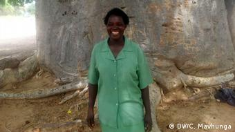 Marcia Matsika is standing in front of the trunk of a huge baobab.