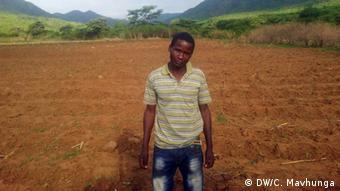 Gilbert Chakasikwa stands in a cultivated field in the foothills of a mountain range.