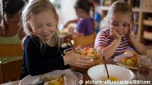 Maja (l) und Frieda (r) teilen am 19.06.2014 in einer Integrationsgruppe in der Kindertagesstätte _Plappersnut_ in Wismar (Mecklenburg-Vorpommern) Salat aus einer Schüssel aus. In der Integrative Kindertagestätte werden bis zu 180 Kinder in 12 Gruppen betreut. Für die spezielle Förderung der Kinder stehen eine Kinderküche, eine Töpferei, die Holzwerkstatt und Therapieräume zur verfügung. Foto: Jens Büttner