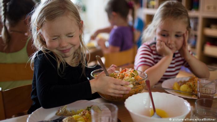 Kinder teilen in einer Kindertagesstätte Salat aus einer Schüssel aus (Foto: picture-alliance/dpa/J. Büttner).