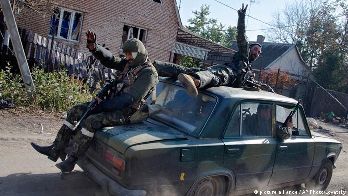 Пророссийские сепаратисты едут на легковом автомобиле по улице Донецка