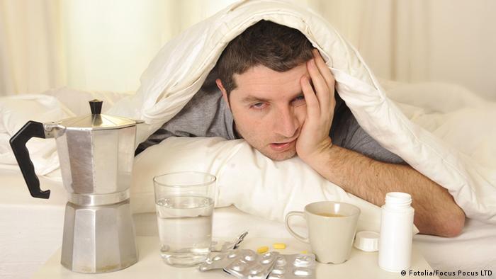 Junger Mann mit Kater im Bett, vor ihm stehen Tabletten und Kaffee (Fotolia/Focus Pocus LTD)