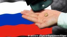 Hand mit einer Rubel Münze, Russischer Flagge und Geldbörse vor dunklem Himmel.
