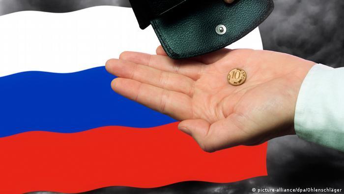 Монета в 10 российских рублей на ладони и флаг России