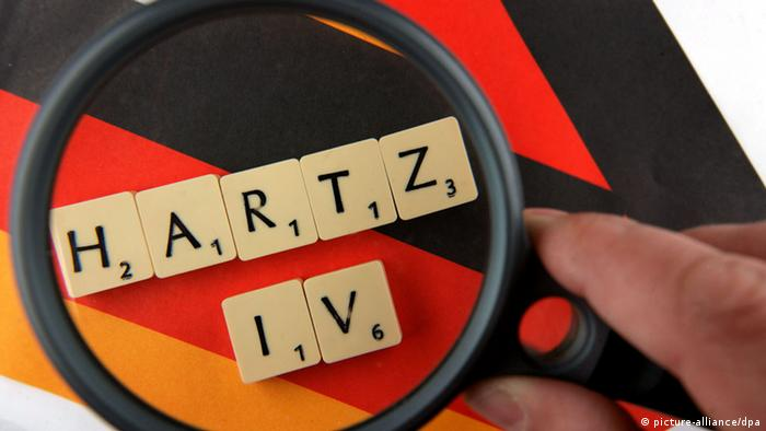 The word Hartz IV appears under a magnifying glass
