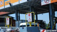 #DSC_6565.JPG Titel: Matola Mautstelle Schlagworte: Matola, Maut, Autobahn, Südafrika Ort: Matola, Provinz Maputo, Mosambik Fotograf: Johannes Beck (DW) Datum: 15.09.2014 Beschreibung: Mautstelle in der Stadt Matola an der Autobahn EN4 zwischen Maputo und Witbank, Südafrika (via Ressano Garcia). Alle Fahrzeuge müssen Maut entrichten. Die Straße ist eine der wenigen Mosambiks, die vierspurig ausgebaut sind.