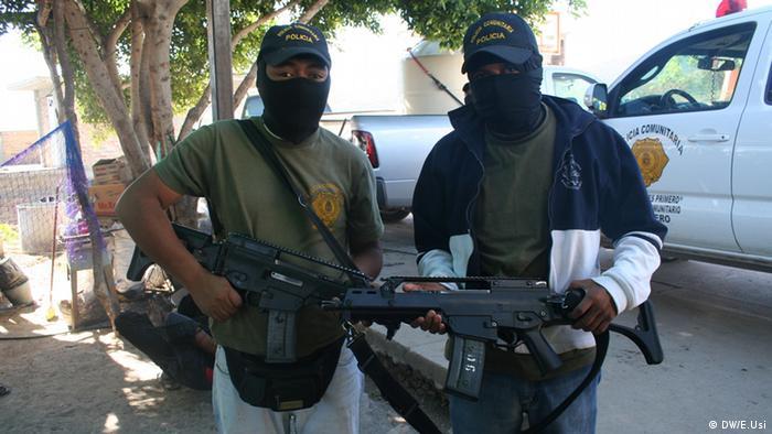 Dois homens encapuzados segurando fuzis no México