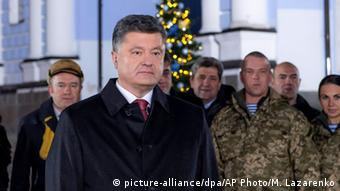 Ukraine's President Petro Poroshenko stands during his address to the nation a few moments before the New Year near the St.Michael Cathedral in Ukraine's capital Kyiv Wednesday, Dec.31, 2014. (AP Photo/Mykola Lazarenko, Pool)