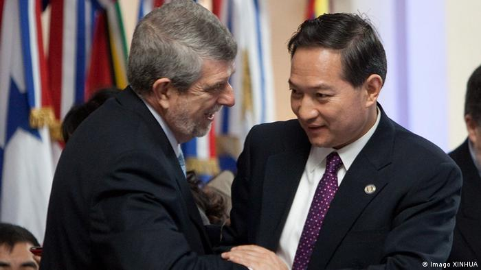 Zhang Kunsheng, right, greets Cuban Vice Foreign Minister Marcos Rodriguez Costa in this 2011 archive image.