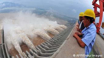 Workers watch as water is released from the Three Gorges Dam, a gigantic hydropower project on the Yangtze river, in Yichang, central China's Hubei province, after heavy downpours in the upper reaches of the dam caused the highest flood peak of the year (Photo: STR/AFP/GettyImages)