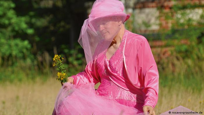Rosa von Praunheim geht in einem rosa Gewand über eine Wiese