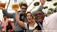 Die Wiesngäste Patrick Devine, (l-r), Amy Sears und Oye Odewunmi aus den USA feiern am 27.09.2014 im Hofbräuzelt auf dem Oktoberfest in München (Bayern). Das größte Volksfest der Welt, die Wiesn, dauert noch bis zum 05. Oktober 2014. Foto: Felix Hörhager/dpa +++(c) dpa - Bildfunk+++