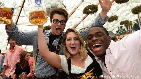 Oktoberfest 2014 - Visitors from the USA Holding beer glasses and wearing traditional Bavarian costumes