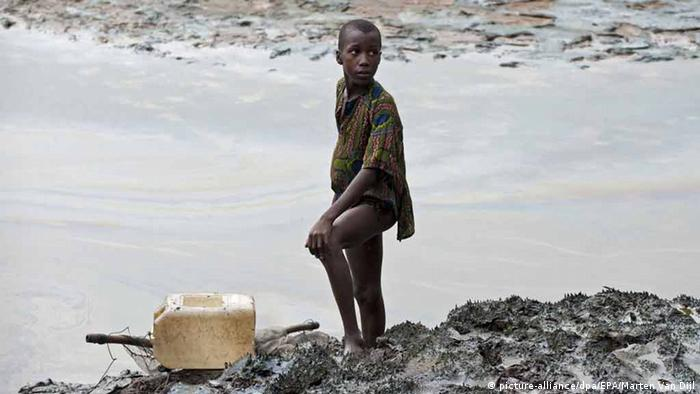 A boy with a fishernet standing next to the oil-stained bank of a creek (picture-alliance/dpa/EPA/Marten Van Dijl)
