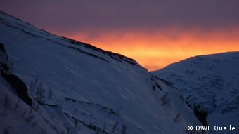 Sun setting over snow covered hills