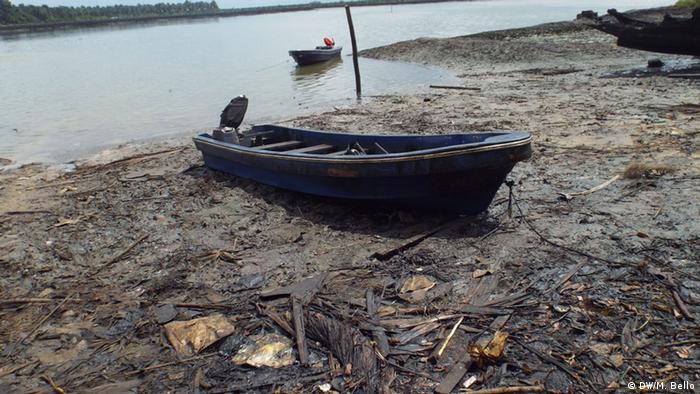 A boat lies on an oil-covered shore. (Photo: Mohammad Bello)