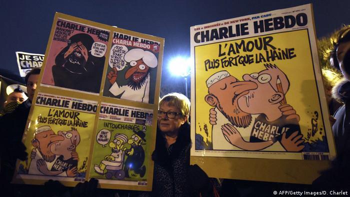 Плакаты с карикатурами из Charlie Hebdo в руках демонстрантов в Париже