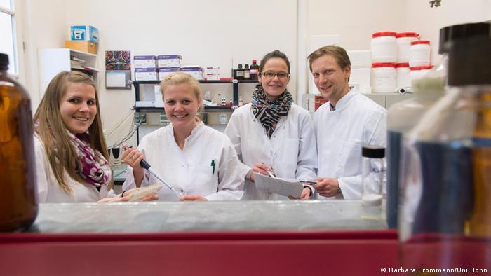 Vier Forscher in weißen Kitteln in einem Labor. (Foto: Barbara Frommann/Uni Bonn)