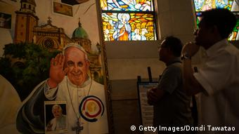 Parish priests look at a montage of paintings of Pope Francis adorning a section of Manila Cathedral on January 7, 2015 in Manila, Philippines (Photo: Dondi Tawatao/Getty Images)
