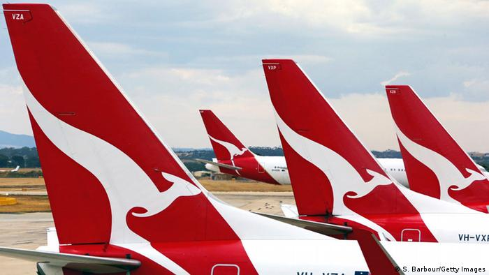Airplanes with the Qantas Airlines logo wait on the tarmac