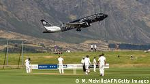 An Air New Zealand jet takes off above the cricketers during day one of the four day warm up International cricket match between New Zealand and England played at the Queenstown Event Center in Queenstown on February 27, 2013. AFP PHOTO / Marty MELVILLE (Photo credit should read Marty Melville/AFP/Getty Images)