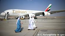 DUBAI, UNITED ARAB EMIRATES - NOVEMBER 18: Businessman walk past an Emirates Airbus A380 during the Dubai Airshow on November 18, 2013 in Dubai, United Arab Emirates. The Dubai Air Show is the premier Middle East air show for trade and business delegates organized by F&E Aerospace. (Photo by Christopher Furlong/Getty Images)