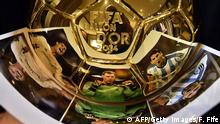 A picture taken on December 15, 2014 shows pictures of (LtoR) Portugal's Cristiano Ronaldo, Germany's Manuel Neuer and Argentina's Lionel Messi reflecting themselves in the Ballon d'Or 2014 trophy displayed at the Mellerio jewelery workshops in Paris. Barcelona's Argentinian forward Lionel Messi, Bayern Munich's Gemany's goalkeeper Manuel Neuer and Real Madrid's Portuguese forward Cristiano Ronaldo were shortlisted for this year's Fifa Ballon d'Or, an association football award given annually to the male player who is considered to have performed the best in the previous year. It is awarded by world governing body FIFA after votes from coaches and captains of international teams, as well as journalists from around the world. AFP PHOTO / FRANCK FIFE (Photo credit should read FRANCK FIFE/AFP/Getty Images)
