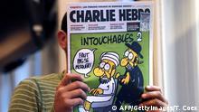 Mann liest Charlie Hebdo-Ausgabe mit Mohammed-Karrikatur auf dem Cover