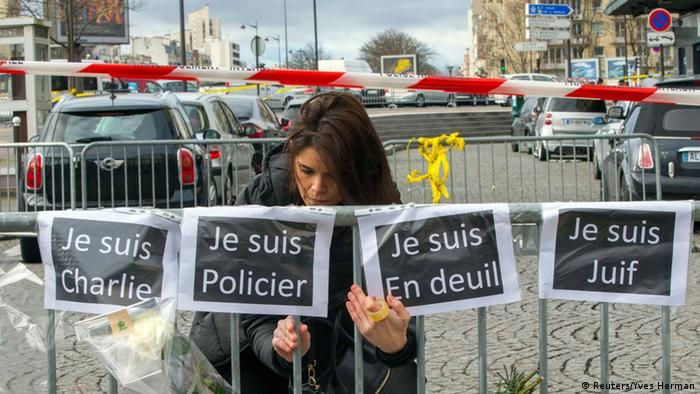 A woman hangs signs reading (from L to R) I am Charlie, I am police officer, I am mourning and I am Jewish while paying tribute to the victims of a hostage taking at the Hyper Cacher kosher supermarket near Porte de Vincennes in eastern Paris January 10, 2015.