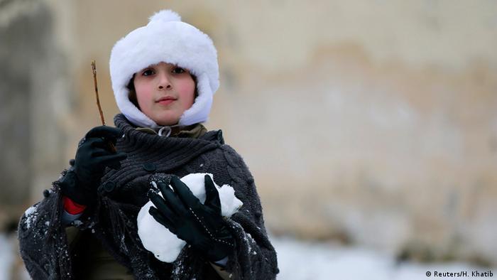 Ein Junge spielt im Schnee in Aleppo, Syrien.