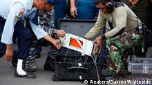 The flight data recorder of AirAsia QZ8501 is lifted out of a carrying case at the airbase in Pangkalan Bun, Central Kalimantan January 12, 2015. Indonesian navy divers on Monday retrieved the black box flight data recorder from an AirAsia airliner that crashed two weeks ago, killing all 162 people on board, a government official said. Flight QZ8501 lost contact with air traffic control in bad weather on Dec. 28, less than halfway into a two-hour flight from Indonesia's second-biggest city of Surabaya to Singapore. REUTERS/Darren Whiteside (INDONESIA - Tags: DISASTER TRANSPORT MILITARY)