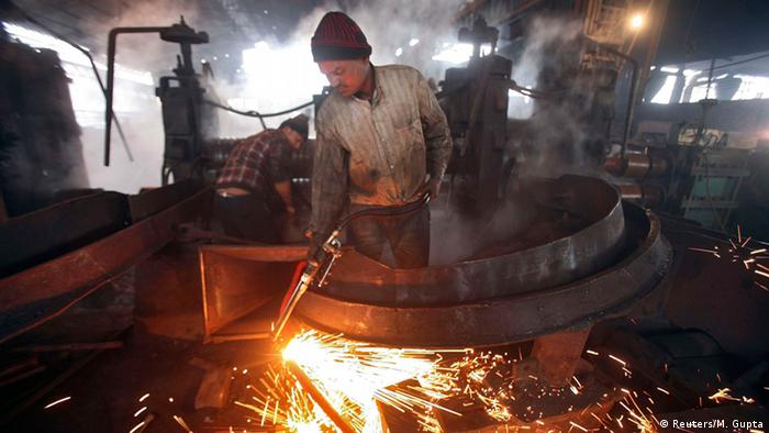 A worker cuts a steel rod inside a steel factory on the outskirts of Jammu
