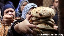 A woman buys bread at a bakery in Cairo, January 8, 2015. The successful roll-out so far of a new smart card system to distribute subsidised bread has been a major achievement for Egypt's government, saving money while earning praise from families who no longer have to wake early to fight for loaves. Picture taken January 8, 2015. REUTERS/Mohamed Abd El Ghany (EGYPT - Tags: FOOD SOCIETY POLITICS BUSINESS)