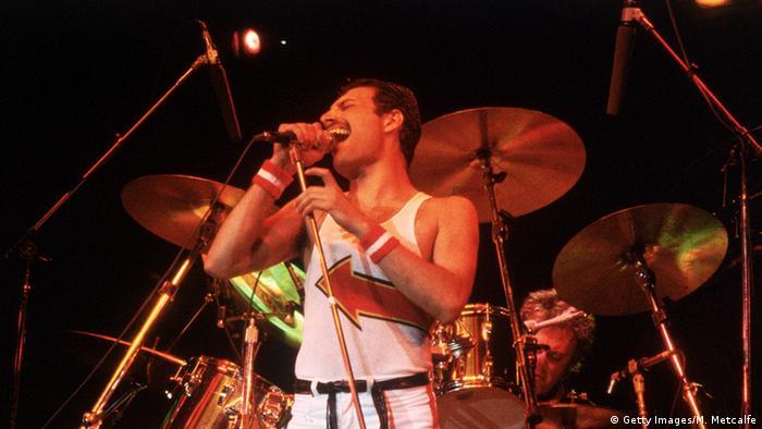 Freddie Mercury steht vor einem Schlagzeug auf der Bühne und singt in ein Mikrofon (Foto: Getty)