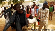 Bildunterschrift:A man injured in a suicide blast is transported at the General Hospital in northeast Nigerian town of Potiskum on January 12, 2015. Four people were killed and 46 injured when two female suicide bombers detonated their explosives outside a mobile phone market in the town on January 11, 2015. Although no one claimed responsibility the attacks bore the hallmark of Boko Haram Islamists who have been increasingly using female suicide bombers in their armed campaign to establish a hardline Islamic state. Potiskum, the commercial hub of Yobe state has been repeatedly attacked by Boko Haram. AFP PHOTO / Aminu ABUBAKAR (Photo credit should read AMINU ABUBAKAR/AFP/Getty Images)