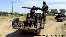 Bildunterschrift:Cameroonian soldiers patrol on November 12, 2014 in Amchide, northern Cameroon, 1 km from Nigeria. The city was raided by Islamists from Nigeria's Boko Haram, killing eight cameroonian soldiers and leading the population to flee on October 15, 2014, before another six coordinated attacks that killed at least three civilians in the remote north of the country, on November 9, 2014. Boko Haram's five-year insurgency in neighboring Nigeria has left thousands dead, and the Islamists have occasionally carried out attacks over the border. Cameroon has deployed more than 1,000 soldiers in the extreme northeast of the country to counter the Islamist threat. AFP PHOTO/REINNIER KAZE (Photo credit should read Reinnier KAZE/AFP/Getty Images)