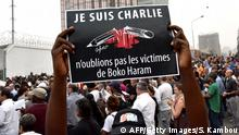 Bildunterschrift:A man holds a placard that reads 'Je suis Charlie, n'oublions pas les victimes de Boko Haram' (I am Charlie, let's not forget the victims of Boko Haram) as people gather outside the French embassy in Abidjan, on January 11, 2015, in tribute to the 17 victims of the three-day killing spree in Paris last week. The killings began on January 7 in Paris with an assault on the Charlie Hebdo satirical magazine in Paris that saw two brothers killing 12 people including some of the country's best-known cartoonists and the storming of a Jewish supermarket on the eastern fringes of the capital which killed 4 local residents. AFP PHOTO / SIA KAMBOU (Photo credit should read SIA KAMBOU/AFP/Getty Images)