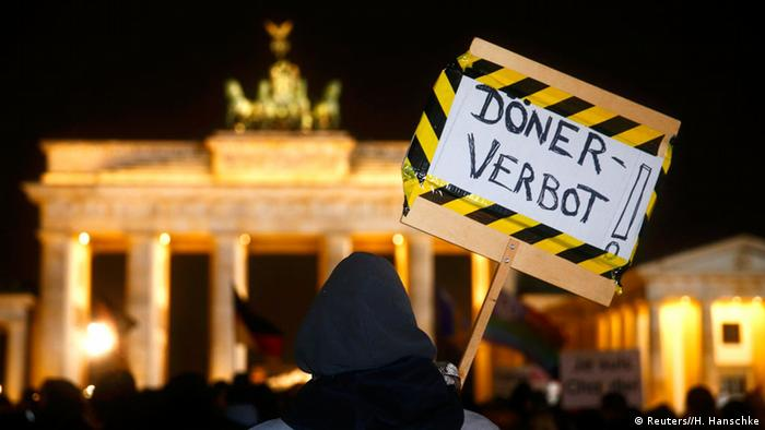 Anti-Pegida-Demonstration: An anti-PEGIDA protester holds a placard reading 'Doner prohibition' as he stands behind members of BAERGIDA, Berlin's section of anti-immigration movement Patriotic Europeans Against the Islamization of the West (PEGIDA) demonstrating in front of the Brandenburg Gate in Berlin January 12, 2015. Copyright: REUTERS/Hannibal Hanschke