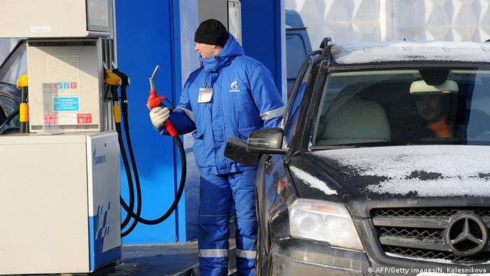 Сотрудник АЗС в Москве заправляет машину