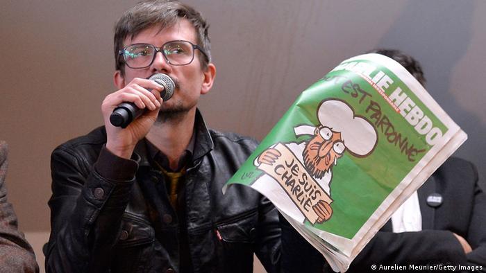 Unter Tränen spricht Rénald Luzier bei einer Pressekonferenz am 13. Januar 2015 über die die erste Ausgabe von Charlie Hebdo nach dem tödlichen Anschlag. In der Hand hält er die Ausgabe mit grünem Titelblatt und Mohammed-Karikatur (Bild: Aurelien Meunier/Getty Images)