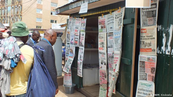 Cameroonians reading newspapers affixed on the street (DW/M. Kindzeka)