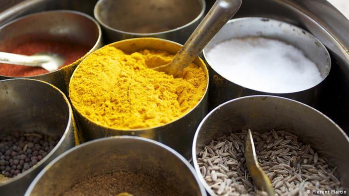 A traditional Indian spice box with yellow turmeric