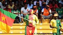 A fan painted in the colours of the Cameroon flag holds up the national flag during the 2015 African Cup of Nations (CAF) qualifier, group D, football match Cameroon vs DR Congo at the Ahmadou Ahidjo stadium in Yaounde on November 15, 2014. Cameroon 1-0. AFP PHOTO/PACOME PABANDJI (Photo credit should read PACOME PABANDJI/AFP/Getty Images)