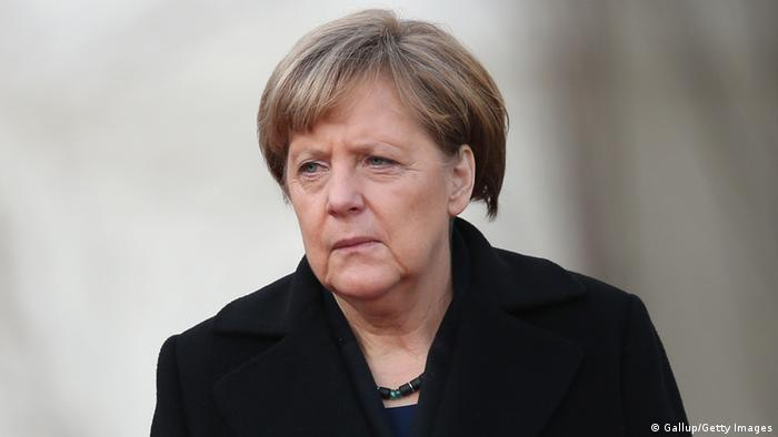Chancellor Angela Merkel dressed in black, grimacing into the distance