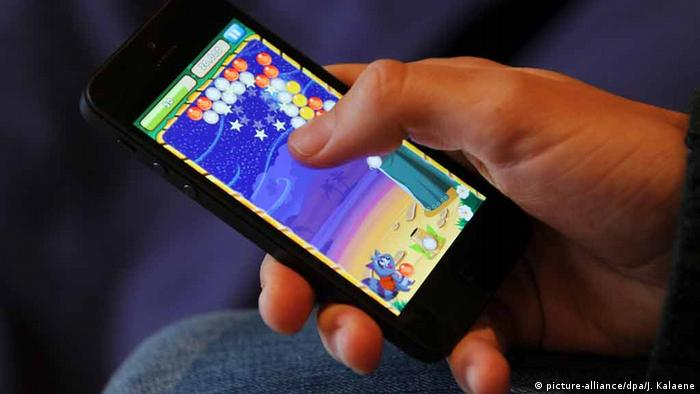 Hand of person playing mobile gaming app Bubble Island (Photo: Jens Kalaene/dpa)